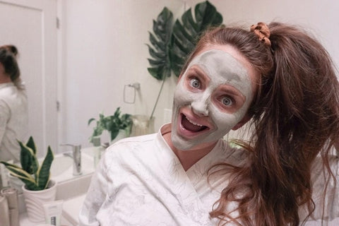 influencer woman in bathroom wearing a clay mask