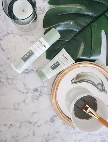NENA Clay Mask and Mineral Toner flat lay with clay bowl and brush