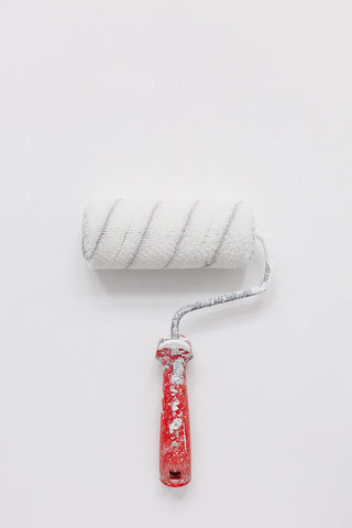 white paint brush with red handle