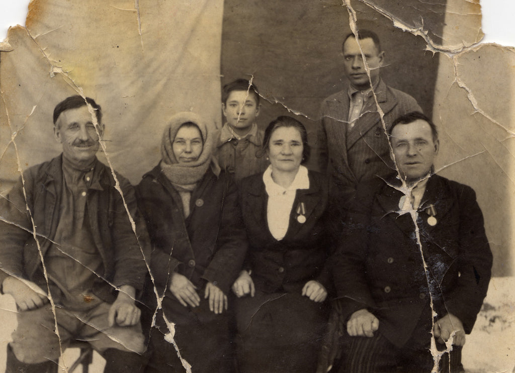 damaged and scratched photo of an old family