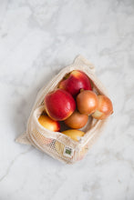 Load image into Gallery viewer, Lifestyle photo of a natural colored mesh produce bag with apples and onions peeking out.