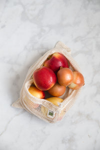Lifestyle photo of a natural colored mesh produce bag with apples and onions peeking out.
