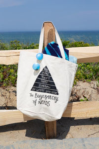 """buyerarchy"" tote with a ocean background on a wood fence with sunglasses and a towel. Buyerarchy is a pyramid reading from top down ""buy, make, thrift, swap, borrow, use what you have"" then underneath the pyramid ""the buyerarchy of needs"""
