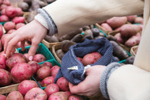 Load image into Gallery viewer, Image of a woman putting red potatoes inside a storm blue mesh produce bag.