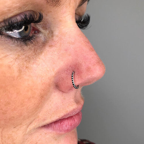 Nose piercing with 14k White Gold and Black Diamond Hinged Ring on a Woman