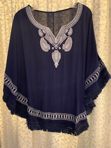 This navy poncho with white embroidery is one size and incredibly light weight!  The embroidery detail at the front top highlights a small v-neck.  There is a wonderful fringe detail along the bottom.  The bottom sides each have a small sewed up section to create a generous arm hole.  You can wear this over a tee shirt or bathing suit.  This piece is so versatile!  100% cotton, hand wash on cool and lay flat to dry.  Or dry clean.