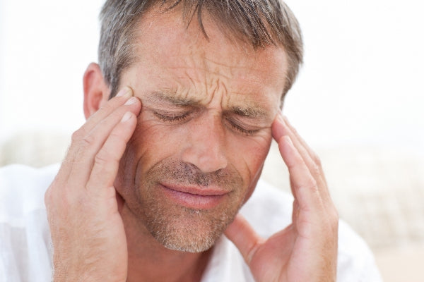 11 Warning Signs of Magnesium Deficiency man wearing white shirt rubbing temples with a headache