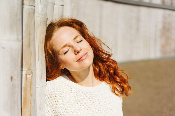 young woman soaking up the sun against a fence