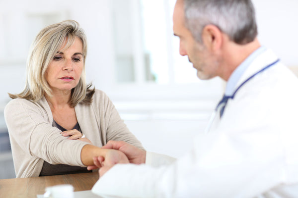 Senior woman consulting with a doctor for her arthritis