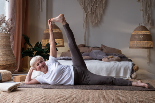 4 exercises for back pain relief senior woman doing lateral leg lift to help with back pain