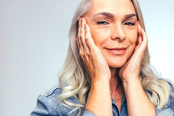 6 turmeric benefits for skin that might surprise you elderly woman with glowing luster lustrous skin touching face wearing blue denim shirt on a gray background