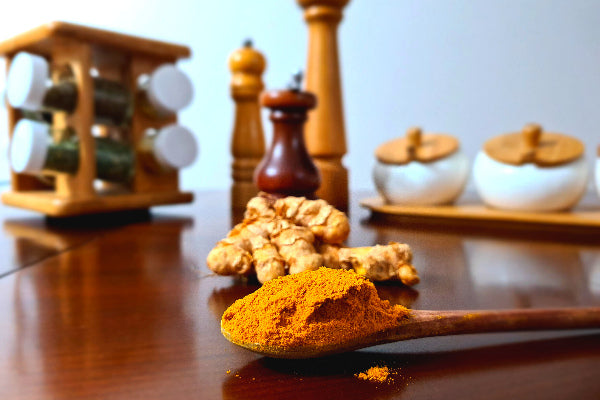 6 turmeric benefits for skin that might surprise you turmeric powder on a wooden spoon turmeric root spice grinders on polished wooden table