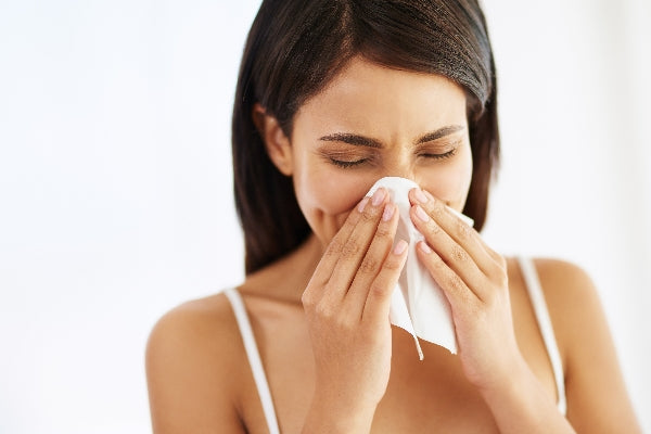 7 Benefits of Vitamin A girl blowing nose into tissue white background