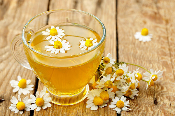 9 chamomile benefits chamomile essential oil benefits backed by science chamomile tea and flowers on a wood table