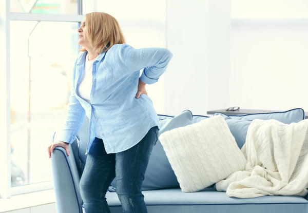 Middle-aged woman grasping her back in discomfort