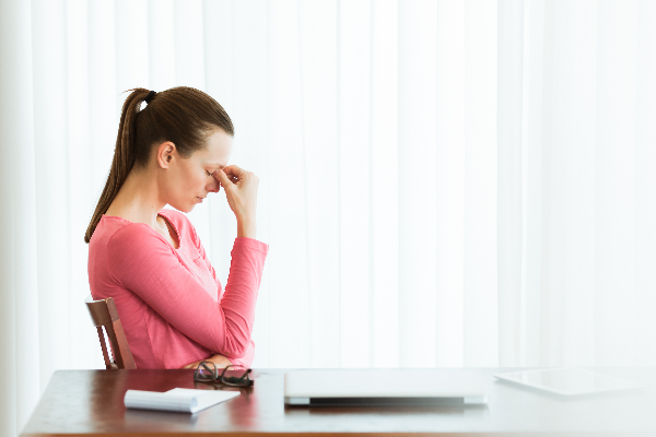 Benefits of Eucalyptus oil woman stressed sitting at wooden table