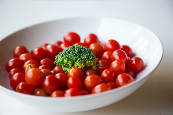 Cherry tomatoes in a bowl with broccoli