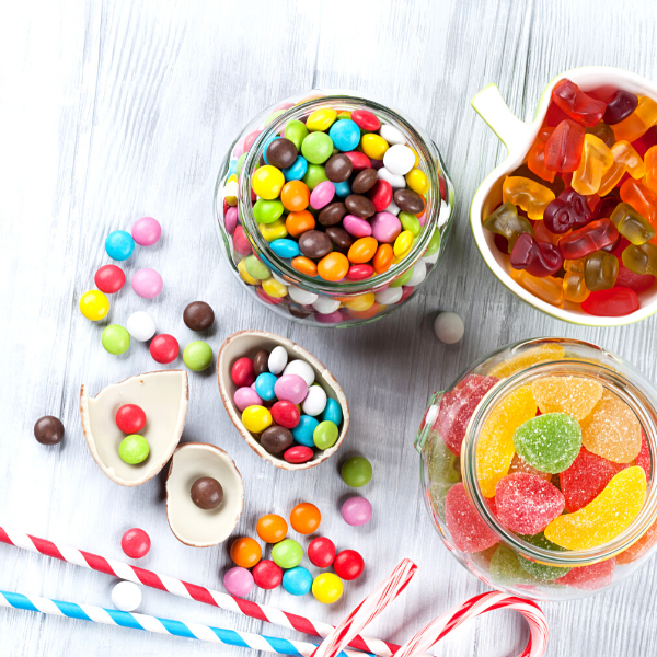 Jars of colorful chocolate covered candy and gummy worms bears with candy canes