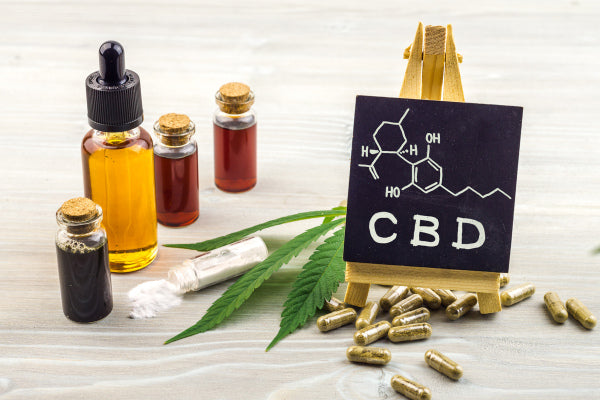 CBG and CBN for Nerve Pain full spectrum CBD in bottles capsules powder on wood table chemical map on chalk board