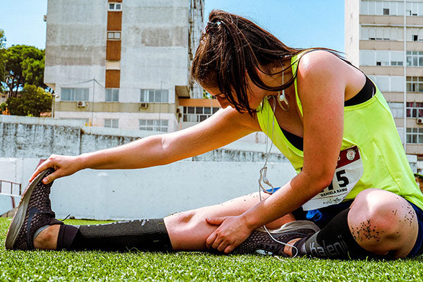 dose of magnesium for muscle cramps does magnesium help cramps in legs woman person soccer player stretching to avoid cramps before activity on grass field