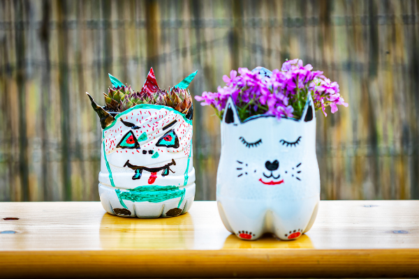earth day reusing plastic bottles diy crafts with a plastic bottle upcycle it hand painted plastic bottles turned into a monster and a cat planter outside on wooden table