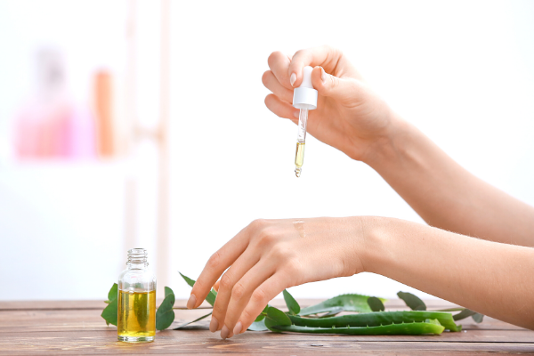 Woman applying essential oil drops to hand with aloe leaves