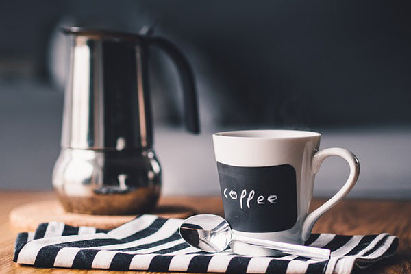 how to relieve muscle soreness fast fast track your recovery from muscle soreness naturally foods for muscle recovery drink coffee mug pot sitting on black and white striped towel on wooden table with spoon beside it