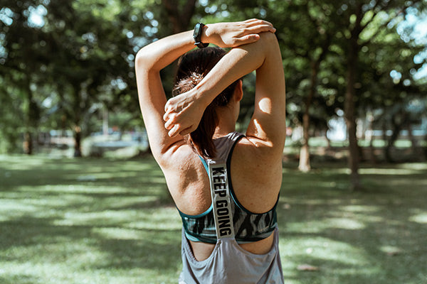 how to relieve muscle soreness fast fast track your recovery from muscle soreness naturally foods for muscle recovery woman stretching before during after exercise to prevent strain soreness outside in park blurred background