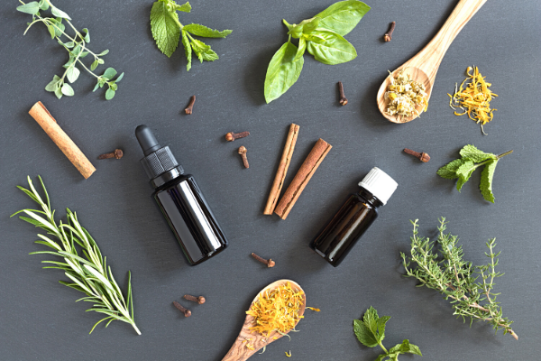 Natural ingredients and tinctures on a black background with leaves and cinnamon sticks