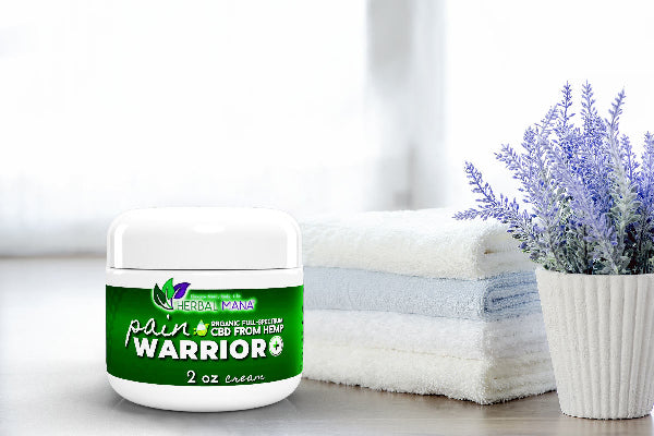 Pain Warrior+ Cream On wood table next to towels and lavender plant