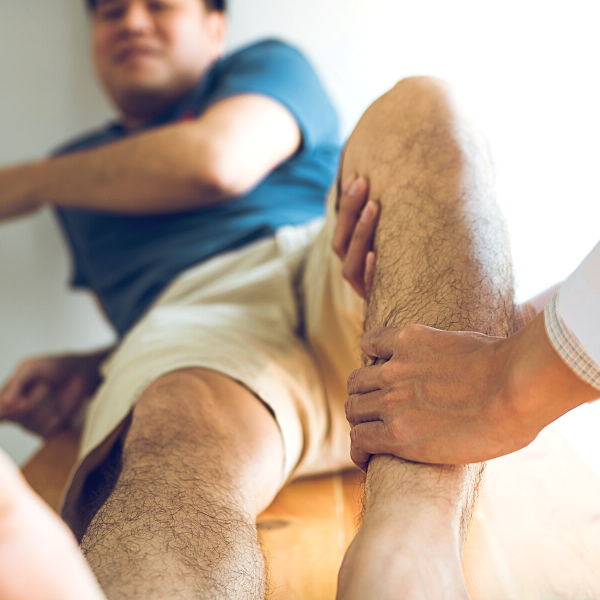Physical therapist massaging man's leg to stimulate blood flow