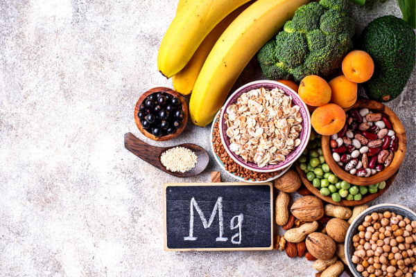 "Foods with magnesium next to a chalkboard with ""Mg"" written on it on a white background"