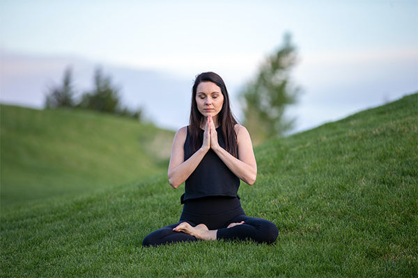 the benefits of meditation meditation types for anxiety relaxation stress depression more woman sitting in a grassy field in the hills meditating wearing black blurred background