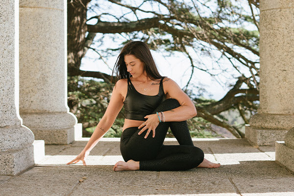 the benefits of meditation meditation types for anxiety relaxation stress depression more woman stretching meditating in between stone granite columns with tree in the background
