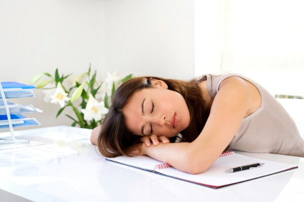 Tired woman sleeping at work - symptom of vitamin deficiency