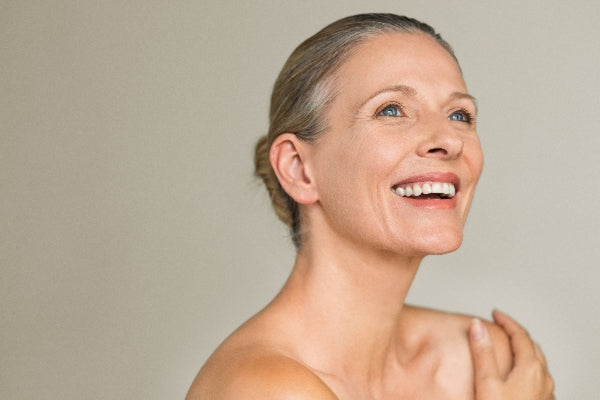 Vitamin A for Immune System Boost middle aged woman smiling with healthy skin on tan background