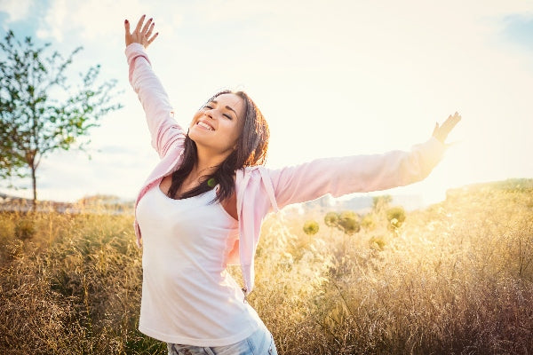 What are the Health Benefits of Vitamin B12 girl in a field under the sun smiling arms above her head happy