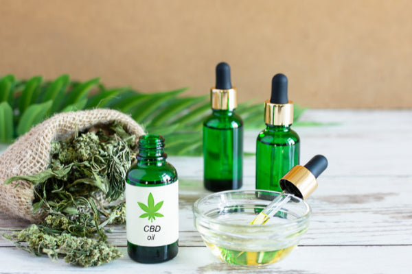alternatives to ibuprofen natural remedies for pain cbd oil in green glass jars with dry flower on wooden table