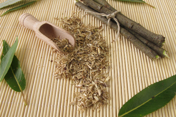 alternatives to ibuprofen natural remedies for pain willow bark sitting on bamboo mat with scoop close up