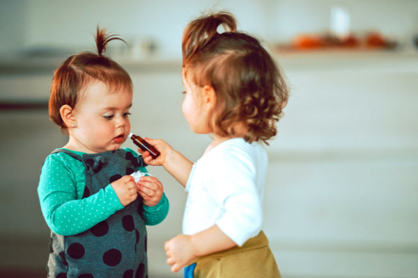 baby safe essential oils what you can use diffuse around kids two small girls smelling essential oil
