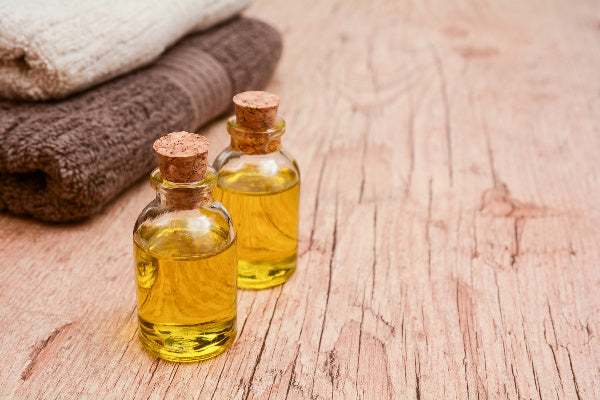copaiba uses and benefits how to use copaiba oil for pain copaiba oil sitting on rustic wooden table with tan and brown towels folded in the background