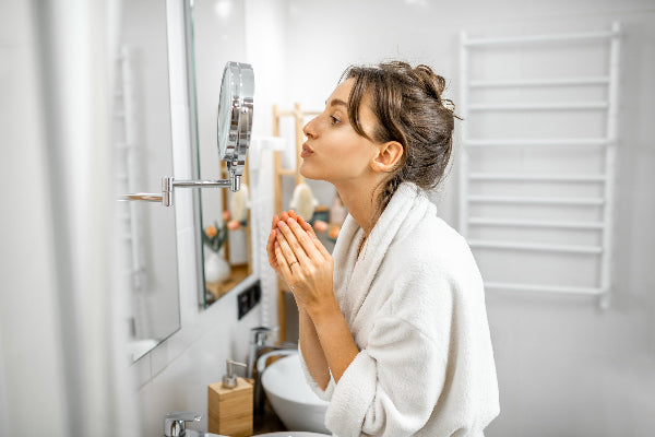 copaiba uses and benefits how to use copaiba oil for pain woman wearing white bath robe in bathroom looking into silver mirror at face acne