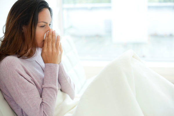 does vitamin b12 boost immune system function woman sitting on couch in light purple sweater blowing nose into tissue with white blanket over legs bright background