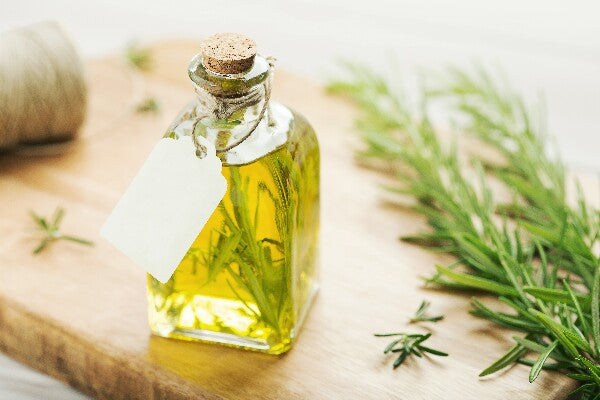 essential oils for nerve pain and neuropathy rosemary oil in clear tincture bottle on wood cutting board with fresh leaves