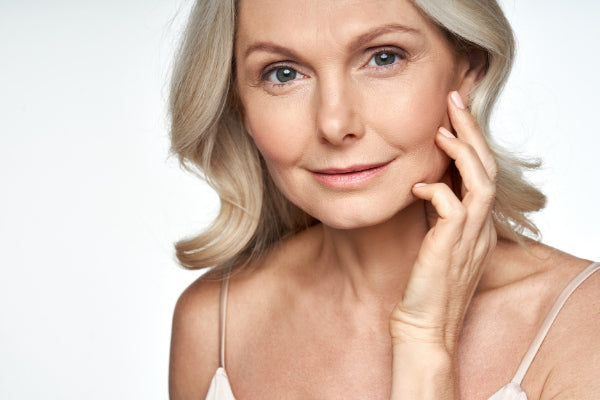 geranium essential oil benefits skin stress nerve pain more middle aged elderly woman touching her face smiling wearing white tank top healthy glowing skin white background