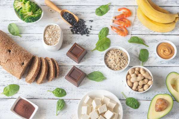 how to correct magnesium deficiency foods with magnesium banana shrimp black beans pumpkin seeds avocado peanuts peanut butter dark chocolate whole grains broccoli on a white rustic wooden table