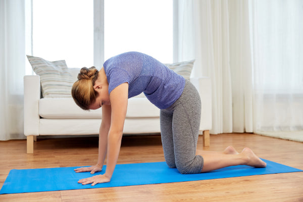 how to stretch your lower back woman doing cat cow stretch pose to relieve lower back pain in living room