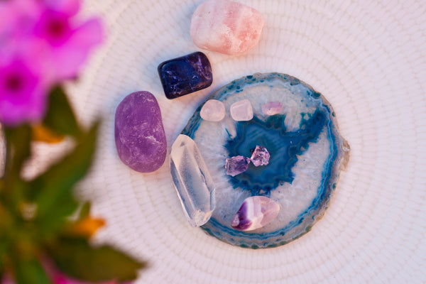 how to use crystals for beginners rose quartz amethyst and more sitting on geode slice close up