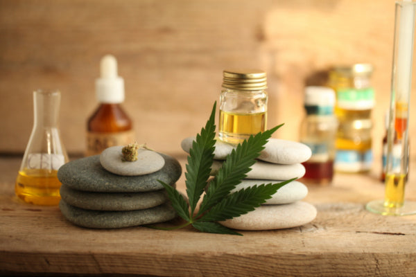 inner warrior for nerve pain cbd leaf oil sitting against and on top op rocks on wooden table
