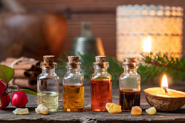 inner warrior for nerve pain essential oils in glass bottles sitting on wooden table with walnut candle close up